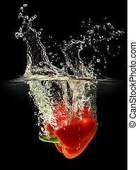Red bell pepper falling in water with splash on black...