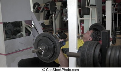 Sportsman flexing chest muscles on bench - Man in yellow...