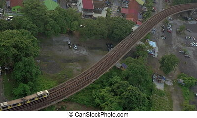 Railway with a passing train in city of Kuala Lumpur,...