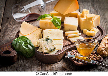 Various types of cheese on cutting board with red wine on...