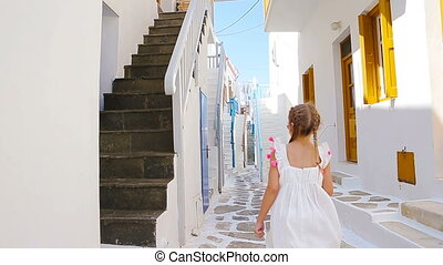 Two girls in blue dresses having fun outdoors. Kids at street of typical greek traditional village with white walls and colorful doors on Mykonos Island, in Greece