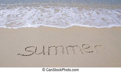 Word Summer handwritten on sandy beach with soft ocean wave...