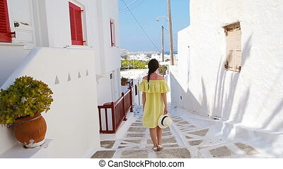 Beautiful woman outdoors in old streets an Mykonos. Girl at...