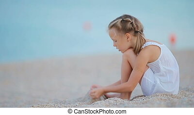 Adorable little girl playing at tropical beach during...