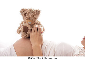 A pregnant woman with a teddy bear on a white background