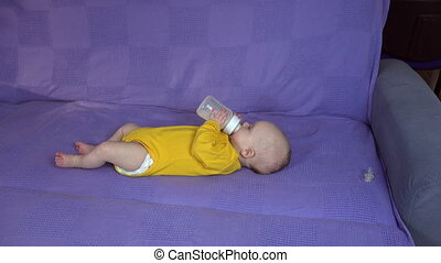 baby with yellow romper drink milk bottle on couch. Baby care. 4K