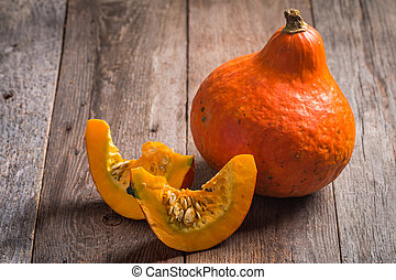 Orange Pumpkins with pieces on wooden background