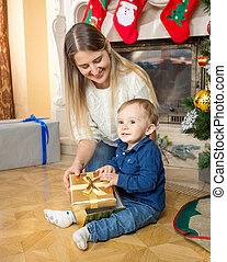 Smiling mother and her baby son with Christmas gift on floor...