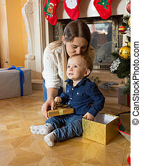 Happy mother kissing her baby son at Christmas tree - Happy...