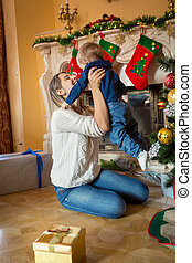 Beautiful mother playing with her 1 year old baby son at...