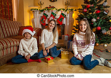 Two cheerful girls with young mother sitting at fireplace in living room decorated for Christmas