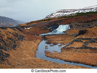 Icelandic Waterfall Fossarrett in Volcanic landscape with...