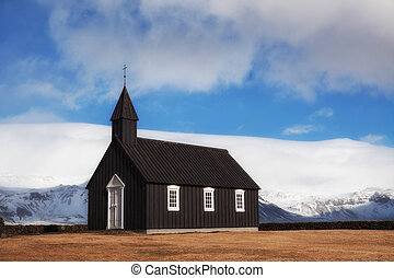 Black Church of Budir in Iceland at daytime with blue sky...