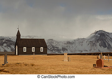 Black Church of Budir in Iceland at daytime with clouds and...