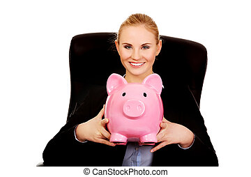 Business woman sitting on armchair and holding piggybank.