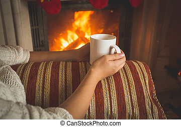 Toned image of woman sitting on sofa at fireplace and...