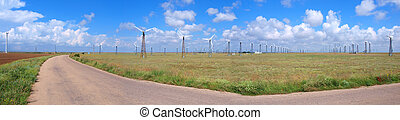 Blue cloudy sky and field with wind-turbines. Panorama