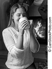 Black and white portrait of beautiful woman drinking tea at the fireplace