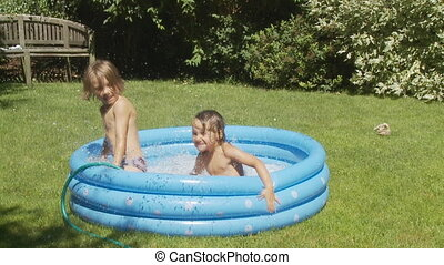 kids jumping in wading pool slo mo - boy and girl jumping in...