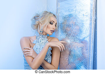 Snow queen near frozen mirror - Beautiful young woman in...