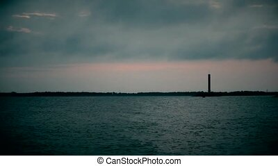 Time lapse of daybreak over water with lighthouse and fast...