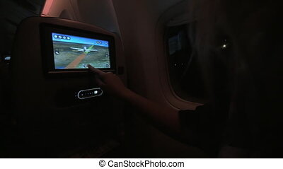 Woman using seat monitor in the plane at night - Woman...