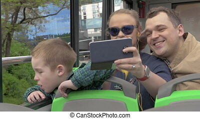 In Vienna, Austria in an open bus rides a young family with...