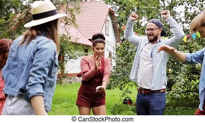 happy friends dancing at summer party in garden - leisure,...