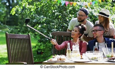 friends taking selfie at party in summer garden - leisure,...
