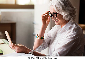 Senious caucasian lady checking her cell-phone - Good news....
