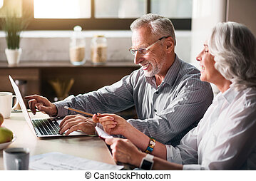 Old man typing while woman pointing at the screen -...