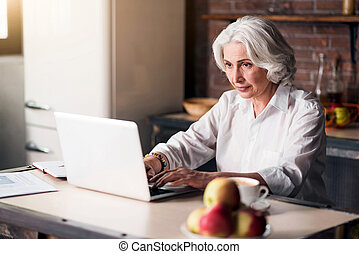 Old good-looking lady using her laptop - You got mail Granny...