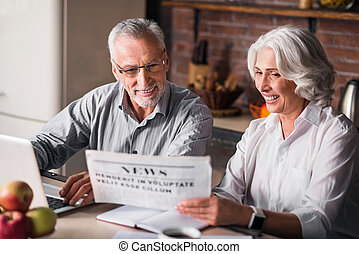 Likable old couple reading newspaper at the kitchen table -...
