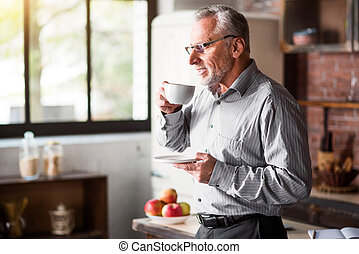 Senior businessman having coffee in kitchen at home -...