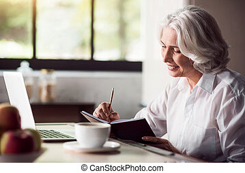 Grey-haired lady taking notes with pencil and using laptop -...