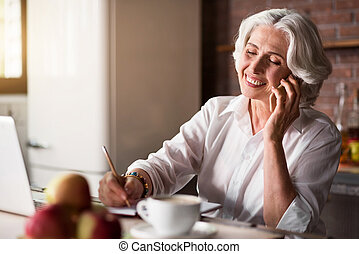 Old woman talking on the phone while taking notes - Smiley....