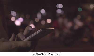 Woman texting on cellphone in night city of Hanoi, Vietnam -...