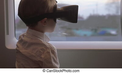 In Saint-Petersburg, Russia in train rides a little boy with virtual reality glasses