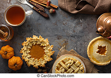 Homemade pumpkin pies decorated with fall leaves copyspace...