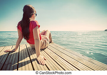 Young woman resting on jetty looking at the calm sea on...
