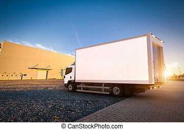 Commercial delivery truck with blank white trailer on cargo...