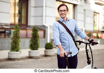 Good looking bespectacled man standing in the street - Happy...