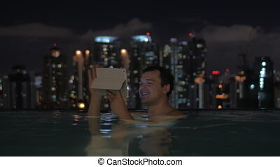 Man with pad in rooftop pool of night Kuala Lumpur - Happy...