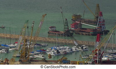 Aerial view of dock when contained barge with sand by crane....
