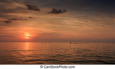 Silhouettes Swim Boat Drifts in Sea at Sunset Sun Reflection...