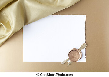 Satin on golden background with blank paper. Flat lay. Top view