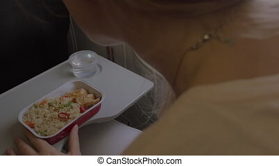 Woman having dinner in the airplane - Woman eating in the...