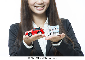 Businesswoman holding a car and house on white background