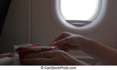 Close up clip of woman eating airplane dinner rise with...