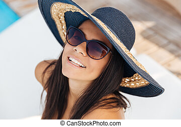 Close-up portrait of brunette girl in hat and sunglasses